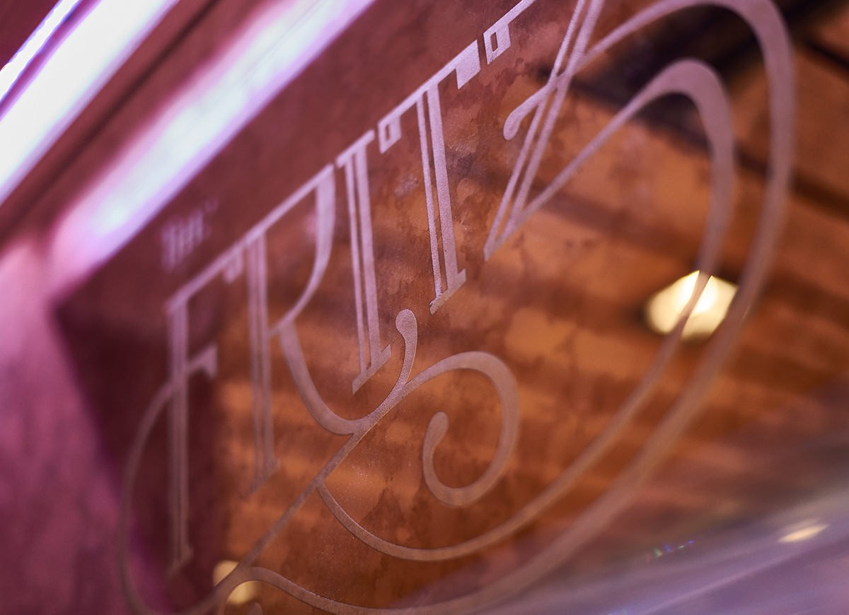The finished logo etched into the speakeasy mirror bar at Vault 634